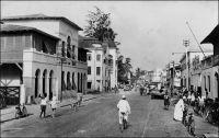 Lomé, la rue du Commerce, au début des années 1950. – La plus ancienne rue commerciale de Lomé, appelée Hamburgerstrasse du temps de la colonie allemande, regroupait la plupart des factoreries de la place, ainsi que le siège local des compagnies maritimes et de négoce. Sur la photo on distingue l'Hôtel du Golfe, suivi du bâtiment de la société John Holt de Liverpool. Un hôtel est déjà signalé dans cette rue, dans les descriptions de la ville à l'époque allemande. L'Hôtel du Golfe est explicitement mentionné  en 1941, dans l'enquête menée par les autorités militaires françaises de Lomé pour éclaircir le passage vers la colonie britannique voisine de la Gold Coast, de deux matelots de l'aviso La Gazelle.
