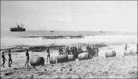 Lomé, frühere landung durch die Brecher.  (Débarquement d'autrefois à travers la barre), vers 1900. - Avant la construction du wharf par les Allemands, entre mars 1902 et janvier 1904, les marchandises, souvent conditionnées dans des tonneaux, étaient confiées aux vagues pour gagner la plage ; les pertes étaient importantes. La population de Lomé comptait, au dénombrement de 1900, quelques 111 Libériens, qui ne sont autres que les Krumen formant les équipages des baleinières et surfboats qui franchissaient la barre pour procéder à la manutention des marchandises auprès des navires au mouillage en rade foraine.