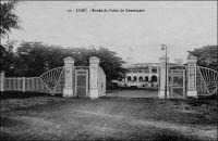 Lomé, entrée du palais du gouverneur – Construit de 18989 à 1905, il abritait les bureaux au rez-de-chaussée et les appartements du gouverneur à l'étage, selon le modèle habituel des bâtiments coloniaux. Le gouverneur August Kohler (1858 – 1902), qui était au Togo depuis 1895, décida en 1898 l'emplacement à 250 m de la plage. Pour que l'ensemble de l'édifice puisse être vu depuis les navires en mer, et ce malgré un talus qui bordait le rivage, le bâtiment reçu un sous bassement de 3,50 m. Sur ce cliché, on distingue, au mat de drapeau du bâtiment, les couleurs françaises. L'édifice devait continuer en effet à abriter l'exécutif du Togo, durant l'occupation britannique, entre 1914 et 1920, puis sous le mandat français et même après l'indépendance, jusqu'à la construction de la nouvelle présidence, sur un terrain mitoyen, en 1970.