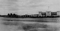 Lomé, Gouvernements-Gebäude. photo F. F. Olympio – Le quartier administratif (yovokomé) et le front de mer. L'imposant bâtiment est le logement administratif allemand (grosses Beantenwohnhaus), où étaient hébergés la plupart des agents supérieurs de la colonie jusqu'en 1908 ; construit entre 1897 et 1901, il est détruit dès 1913. Les fonctionnaires seront ensuite logés par deux dans des maisons de fonction, appelées « bungalow de fonctionnaires », toujours dans le même quartier. La vue est prise depuis le wharf allemand construit en 1903. Le dos de la carte postale n'est pas divisé, ce qui signifie qu'elle remonte à avant 1905 : la photo a donc vraisemblablement été prise en 1904. Fabriano Francisco Olympio, commerçant et photographe à Lomé, est l'un des fils de Francisco Olympio (le fondateur de la branche afro-brésilienne de la famille, né en 1833 à Bahia et arrivé sur la côte ouest africaine dans les années 1850) et le frère d'Octaviano Olympio, lui-même père de Sylvanus Olympio, le premier président du Togo indépendant. Ayant quitté le Togo au début du XXème siècle pour le Cameroun, Fabriano Francisco revint ensuite à Lomé ou il devait mourir en 1910.